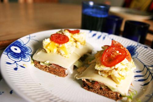 Et stykke med Serrano skinke, lagret ost, scrambled eggs og tomat