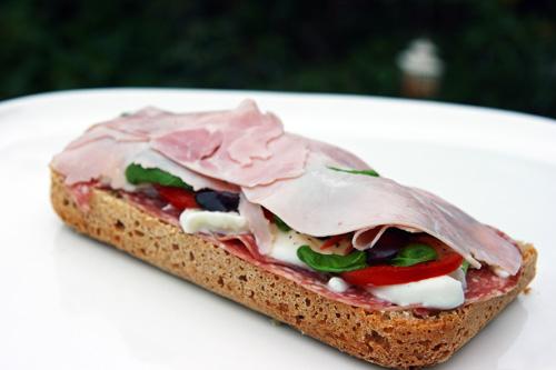 Sandwich med skinke, salami, mozarella, tomater, basilikum, oliven og olivenolie